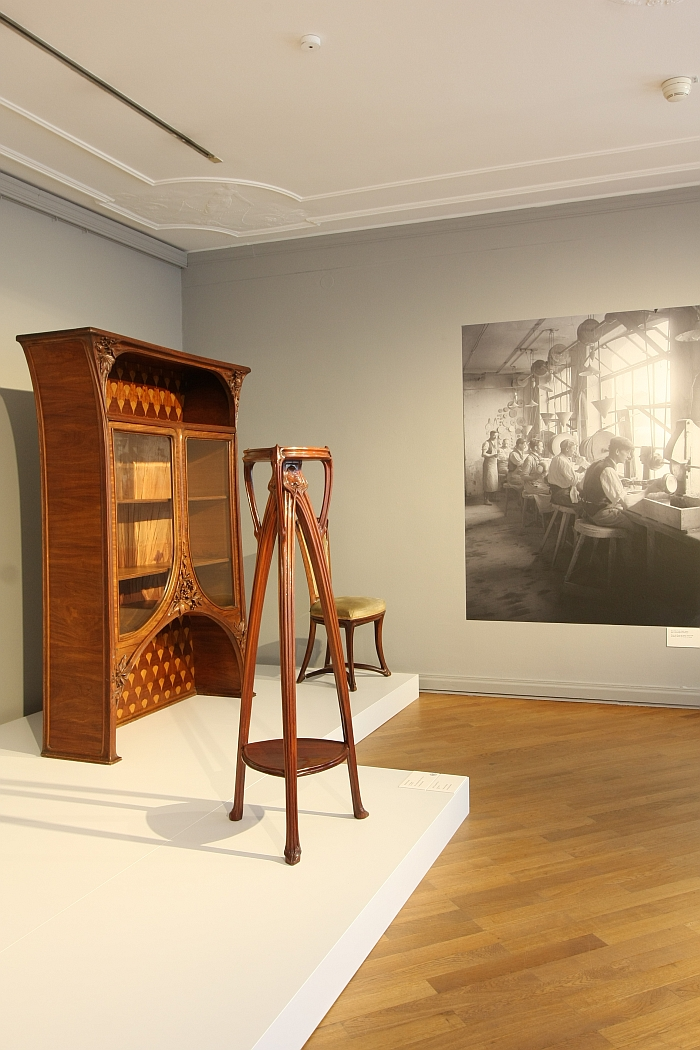 A Sellette, flower stand by Emile André, 1901, a cupboard by Louis Majorelle, 1900/05 and a photo of workers inside the Émile Gallé workshop, Nancy, as seen at Germany versus France. The Struggle over Style 1900-1930, Bröhan Museum Berlin