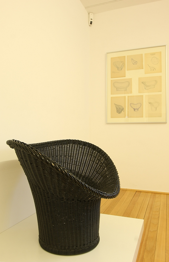 The E20 Korbsessel, in front of sketches of further wicker chairs, as seen at, Der Stuhl des Architekten - Sitzmöbel von Egon Eiermann, Ungers Archiv für Architekturwissenschaft Cologne