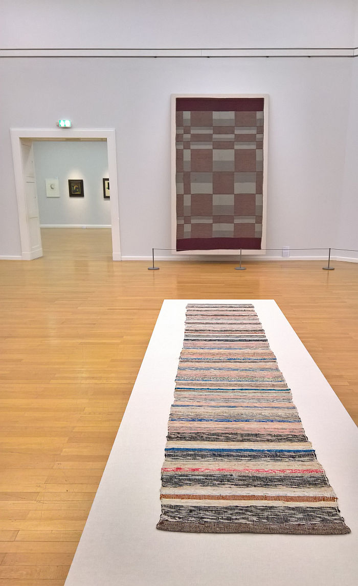 Rag rug by Helene Schmidt-Nonné (foreground) and a wall hanging from Burg Giebichenstein Halle (rear), as seen at Bauhaus. Textiles and Graphics, Kunstsammlungen Chemnitz