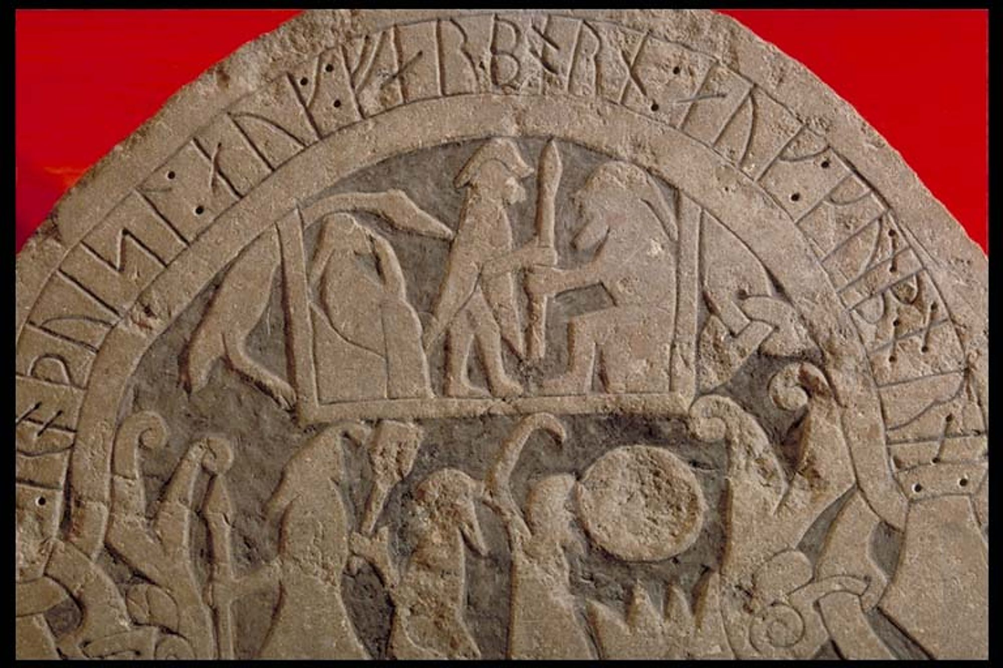Detail of carving from Sanda churchyard, Gotland, potentially showing Valhalla, Odin, Frigg and an enormous duck. Frigg (seated, left) in a kubbstol (photo historiska.se CC BY 2.5 SE)